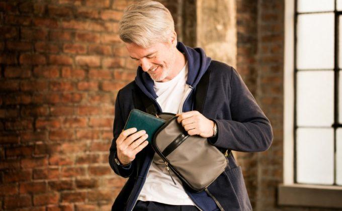 ボディバッグを持ち笑う男性