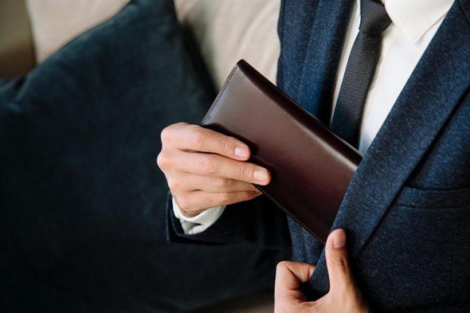 薄い長財布を上着の胸ポケットにしまう男性