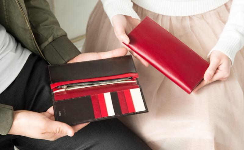 JOGGO(ジョッゴ)の色違いの長財布を持つ男女