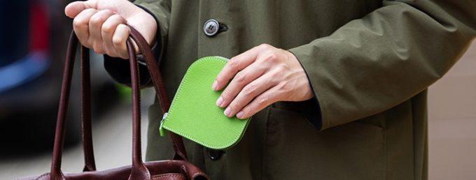 明るい色のコンパクト財布を鞄にしまう男性