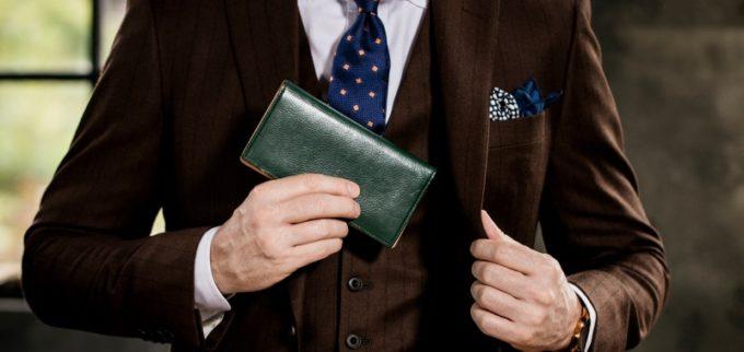 薄型の小銭入れ無し長財布をポケットにしまう男性