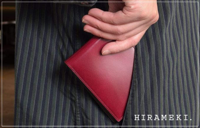 女性がポケットから出すHIRAMEKI.(ヒラメキ)の革財布