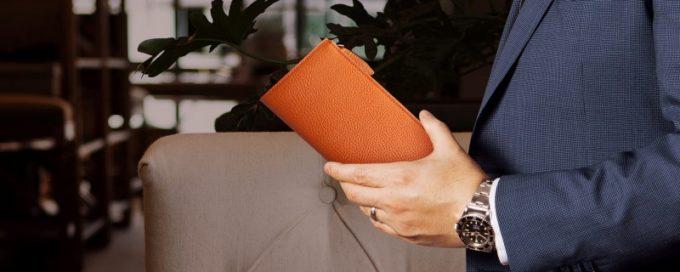 オレンジ色の大人格好良い革財布を持つ紳士