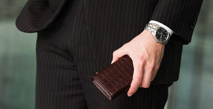 クロコダイルの高級ミニ財布を持つ男性