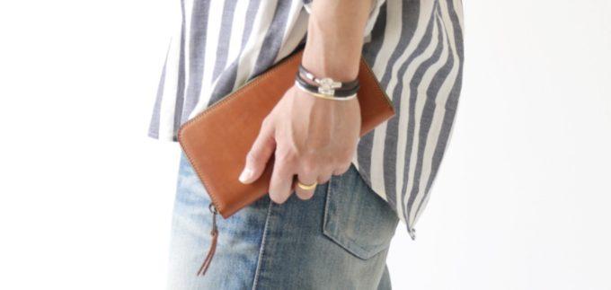 シンプルなラウンドファスナー長財布を持つ若者
