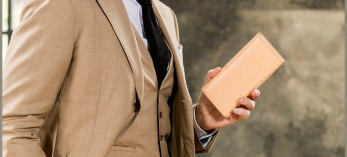 シンプルな長財布を持つ男性