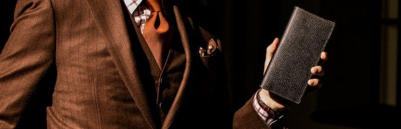 エンボス加工の革財布を持つ紳士