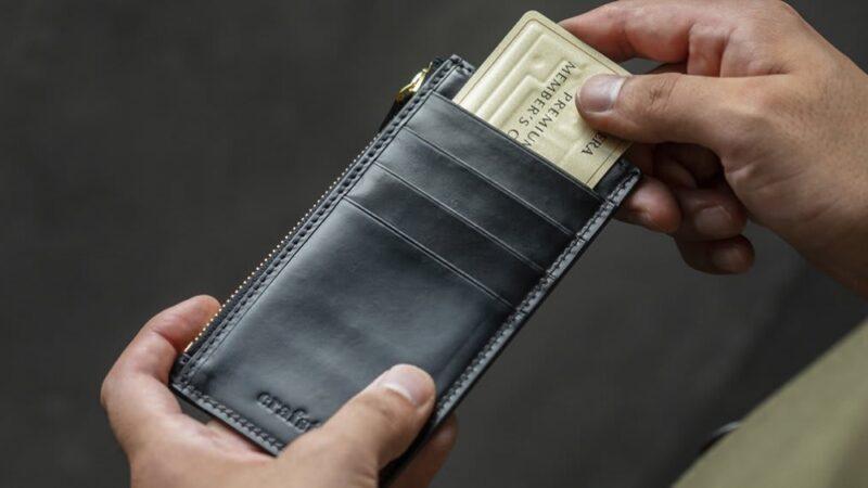 クラフストの財布からカードを取り出す男性